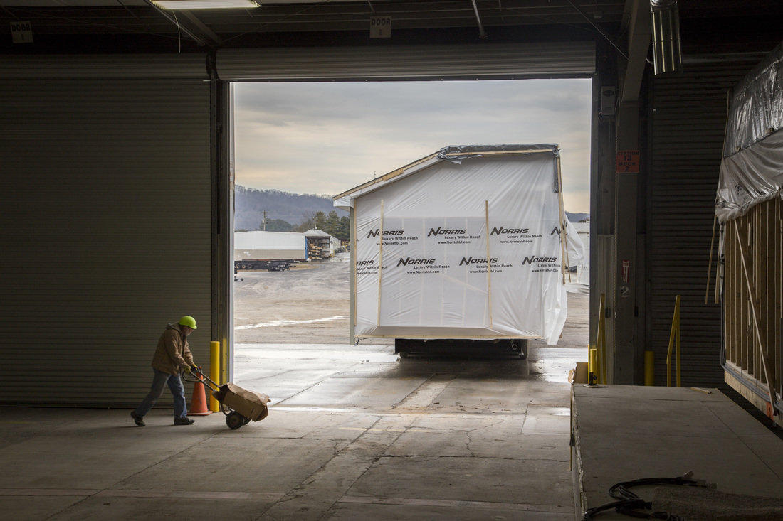 The back of a prefabricated home all wrapped up in plastic as it leaves the home building facility on a trailer.